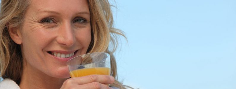 Closeup of a woman in a bathrobe drinking orange juice outdoors